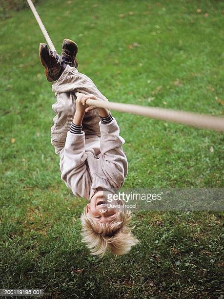 Boy (4-6) hanging upside down on rope, portrait