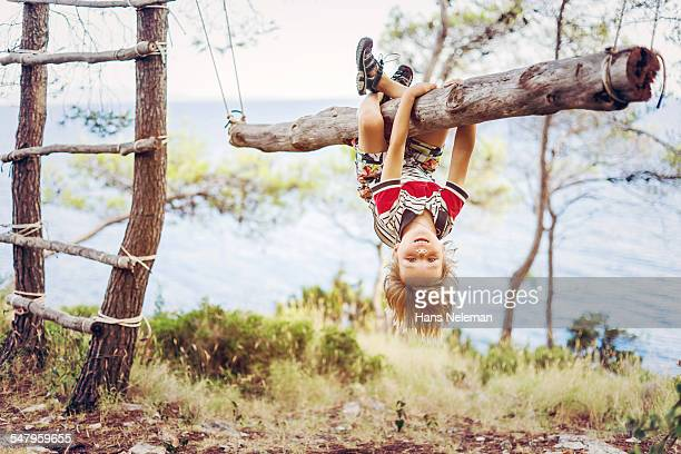 Boy hanging upside down on tree trunk