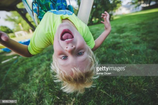 boy hanging upside down - resistencia fotografías e imágenes de stock