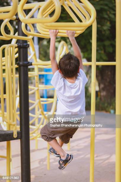 Boy hangs on a bar