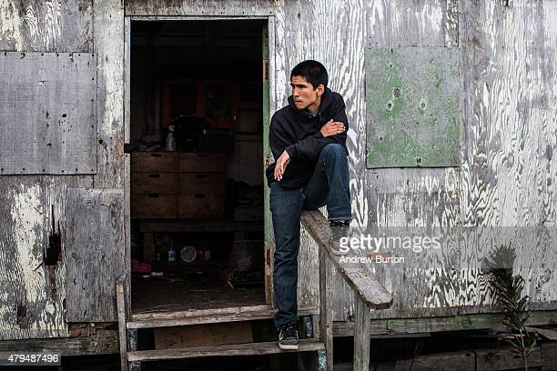 A boy hangs out on the front steps of his greatgrandmother's house on July 3 2015 in Newtok Alaska Newtok is one of several remote Alaskan villages...