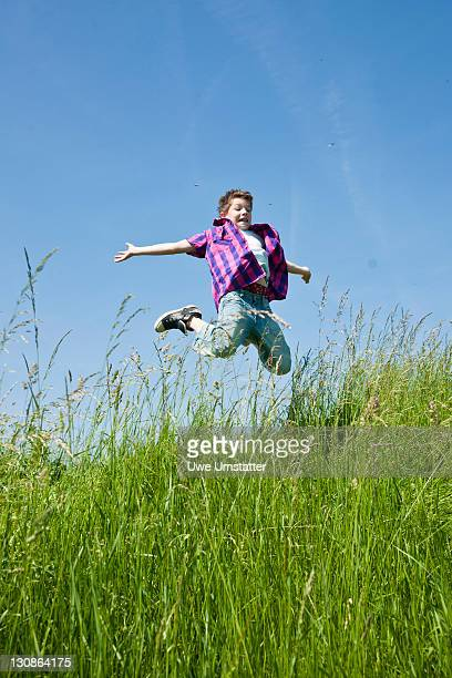 A boy happily jumping in a meadow