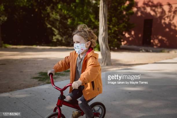 boy happy wearing surgical mask on his bike - real body fotografías e imágenes de stock