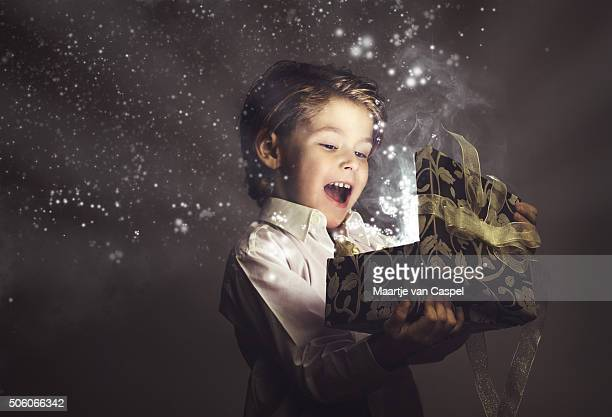 boy happy while opening magic gift, lights and stars - birthday gift stock pictures, royalty-free photos & images
