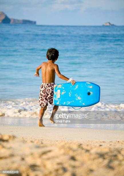 boy has fun with the surfboard at the beach