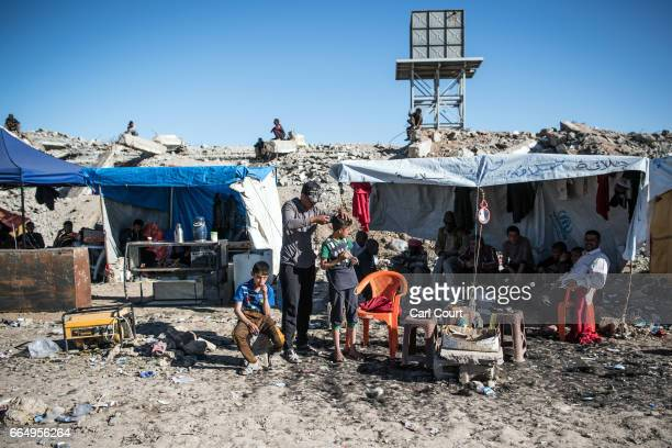 A boy has his hair cut in Hamam alAlil refugee camp where large numbers of people have settled after being displaced by fighting during the offensive...