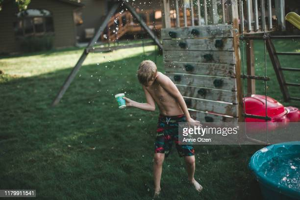 boy haveing a water fight - annie sprinkle stock pictures, royalty-free photos & images