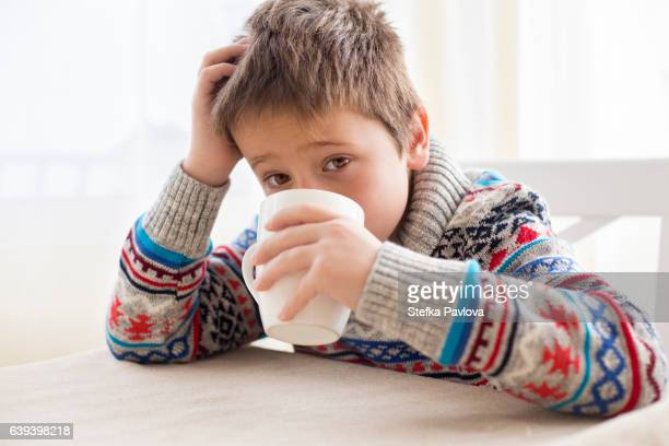Boy having a cold sitting in the kitchen at table drinking a hot drink