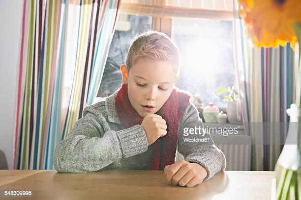 boy having a cold sitting in the kitchen - coughing stock photos and pictures