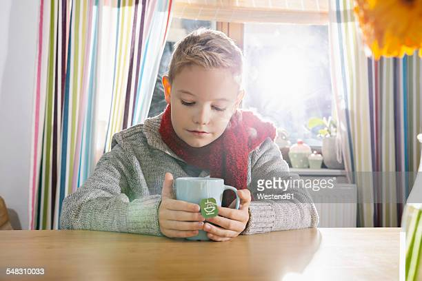 Boy having a cold sitting in the kitchen with cup of tea