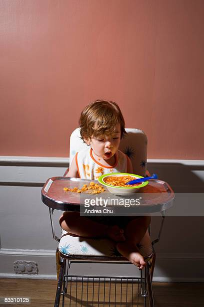 Boy having a messy meal in vintage  highchair.