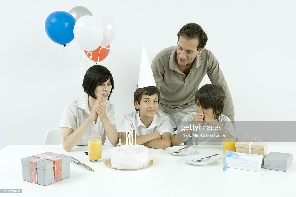 Boy having birthday party with family, looking at camera : Stock Photo