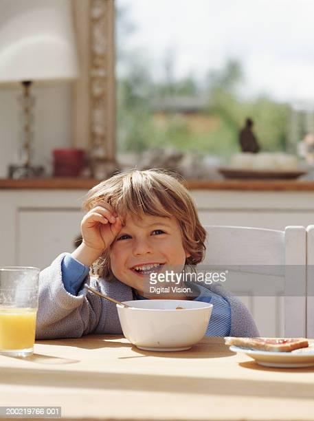 Boy (4-6) having breakfast in kitchen, laughing
