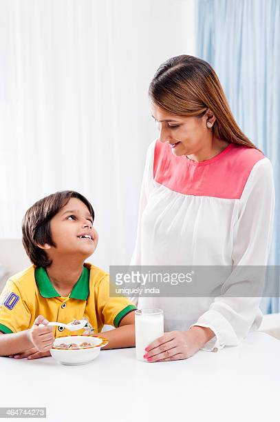 Boy having breakfast with her mother standing beside him