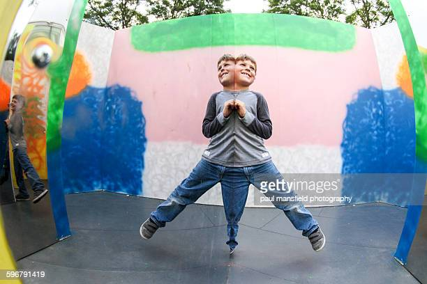 boy having fun creating symmetry with mirror - symmetry stock pictures, royalty-free photos & images