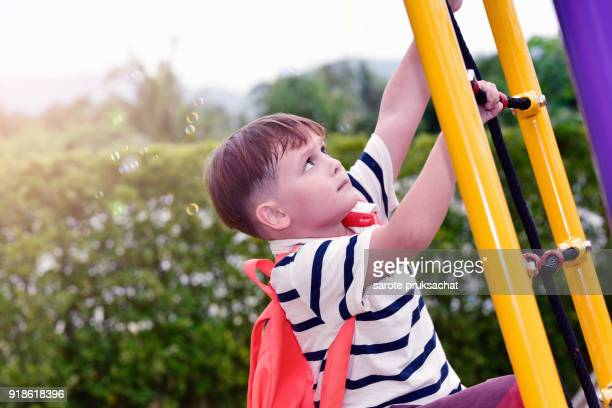 Boy having fun on a playground outdoors in summer. Sport activities for kids  in the international kindergarten playground.