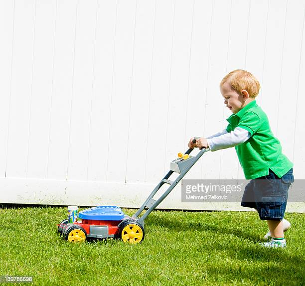 boy having fun with fake lawn mover - fake stock pictures, royalty-free photos & images