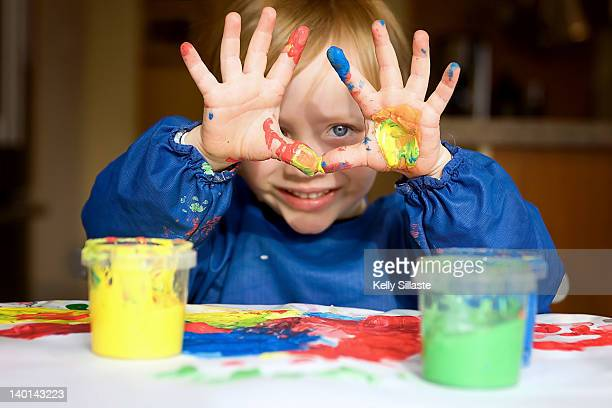Boy having fun with messy fingerpaints