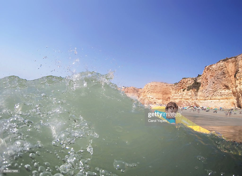 boy having fun with waves in the sea, Algarve, Portugal