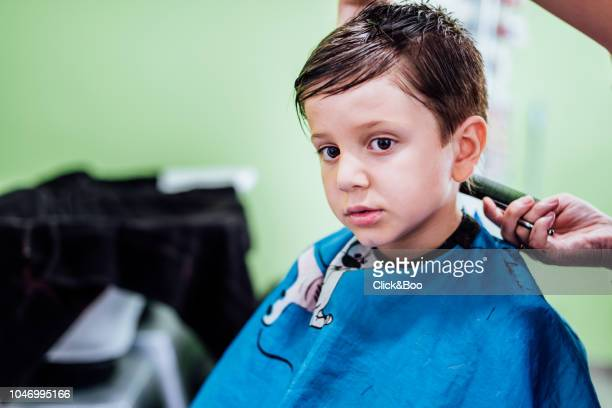 Boy having haircut in hairdressing in a blue coat