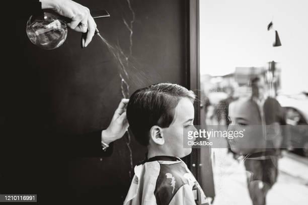 boy having haircut in hairdressing - click&boo fotografías e imágenes de stock