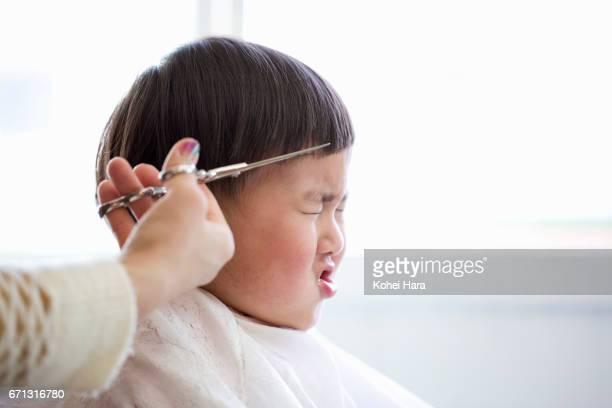 A boy having his hair cut by female beautician in a beauty salon