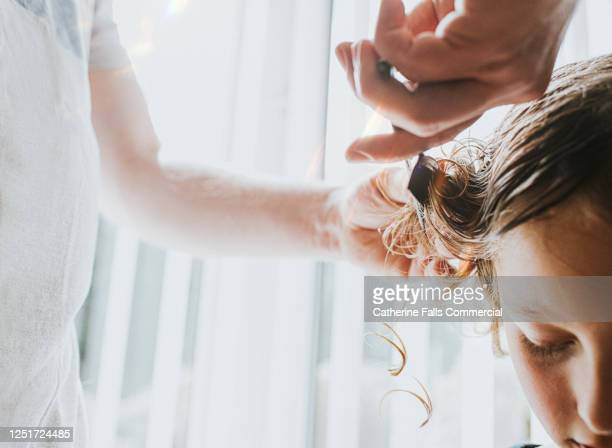 boy having his long blonde hair cut - extra long stock pictures, royalty-free photos & images