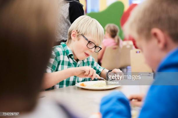 boy having lunch at table in school cafeteria - cantine photos et images de collection