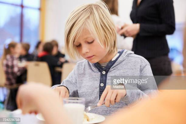 boy having lunch in school cafeteria - cantine photos et images de collection