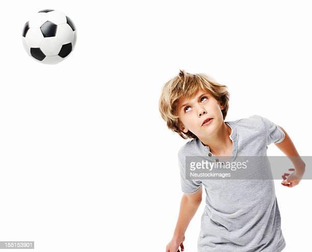 Garçon en direction de ballon de football, isolé