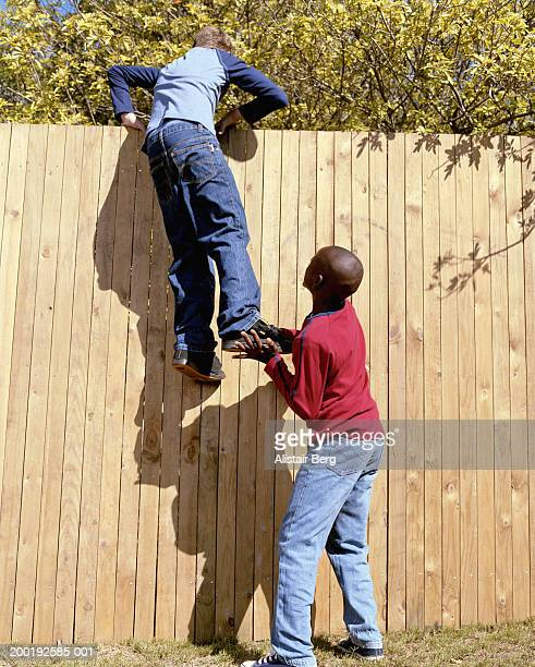 boy (11-13) helping another boy (11-13) climb fence, rear view - reggere foto e immagini stock