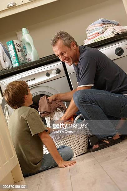 Boy (9-11) helping father load washing machine