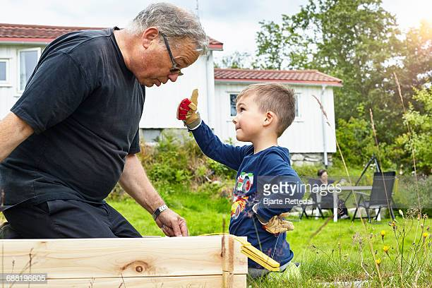 Boy helping Grandfather with joinery