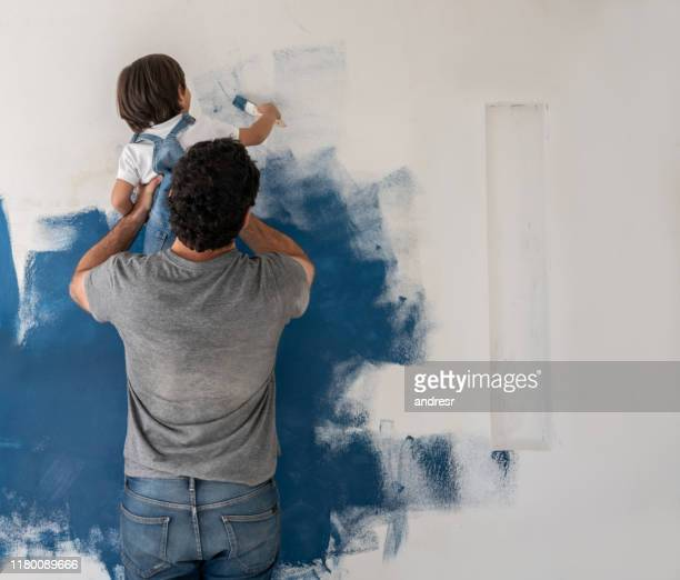 boy helping his father painting the house - dipinto foto e immagini stock