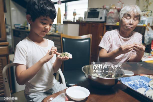 Boy helping his grandmother prepare food