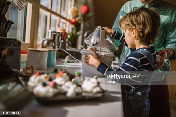 boy helping his mother mixing whipped cream - electric mixer stock pictures, royalty-free photos & images