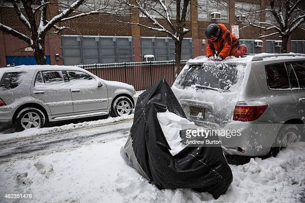 A boy helps his dad clean snow off their car the morning after a snowstorm on January 27 2015 in New York City The storm which was predicted to dump...