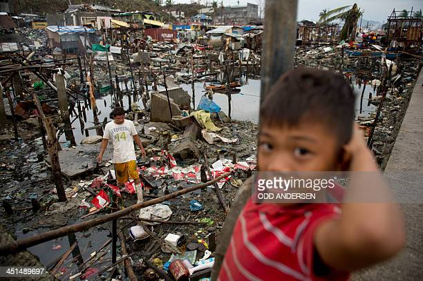 A boy helps his father slavage belongings from their destroyed house after Super Typhoon Haiyan ripped through this waterfront community two weeks...
