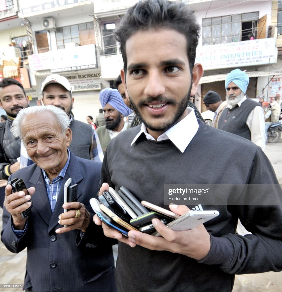 A boy helps the voters with new type of service to keep the mobile phones safe outside with him at the polling station in village Matour on February..