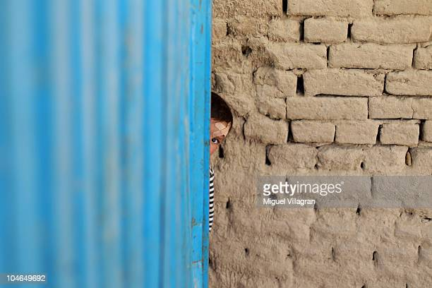 A boy hides behind the back of a small store on October 2 2010 in Feyzabad Afghanistan Germany has more than 4500 military forces in Afghanistan as...