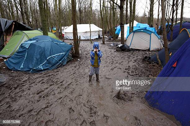 A boy hides his face in his hood as he negotiates thick mud in a new migrant camp on January 6 2016 in Dunkirk France Thousands of migrants continue...
