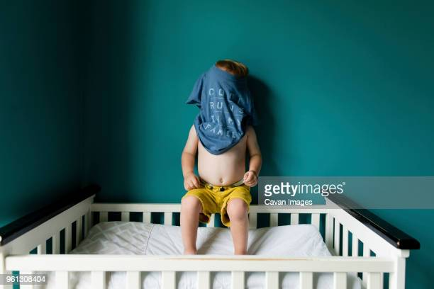 Boy hiding face with t-shirt while sitting on railing