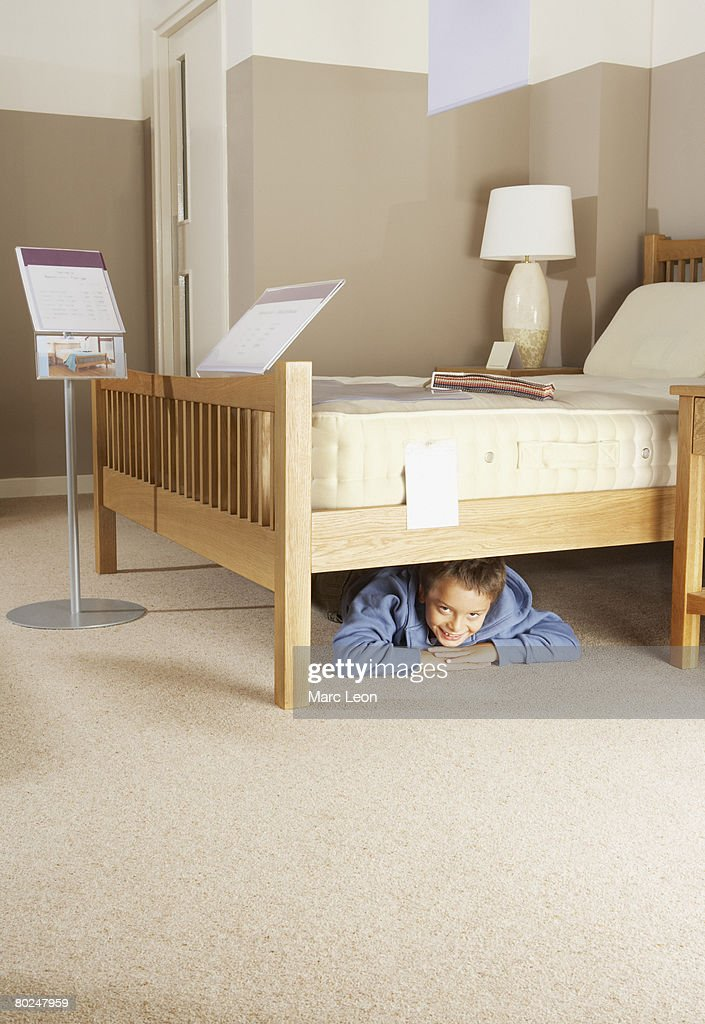 Boy Hiding Under Bed In Furniture Store Stock Photo