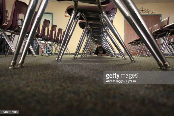 Boy Hiding Under Chairs In Room