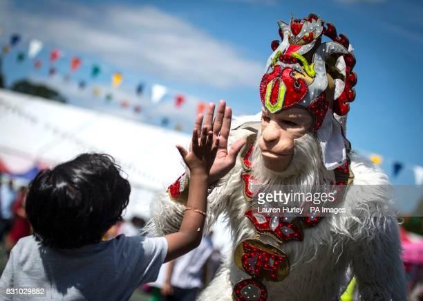 A boy highfives a man dressed as Hindu monkey god Hanuman during the Janmashtami Hindu festival at the Hare Krishna Bhaktivedanta Manor in Watford an...
