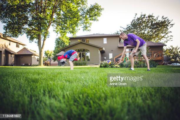 boy hiking a football to his dad - snapping the ball stock pictures, royalty-free photos & images