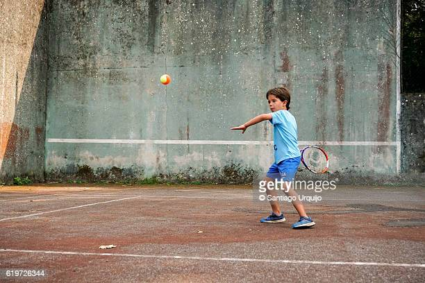 Boy hitting a forehand while playing tennis