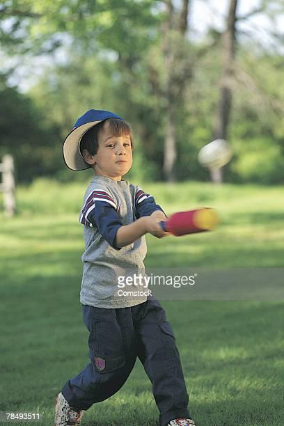 Boy hitting baseball in backyard