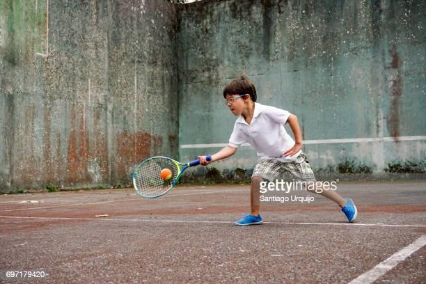 Boy hitting the ball while playing tennis