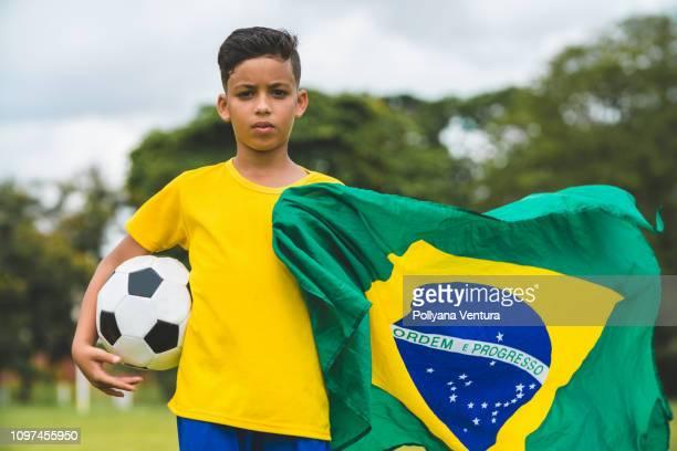 garçon tenant un ballon et le drapeau du brésil - tenue de football photos et images de collection